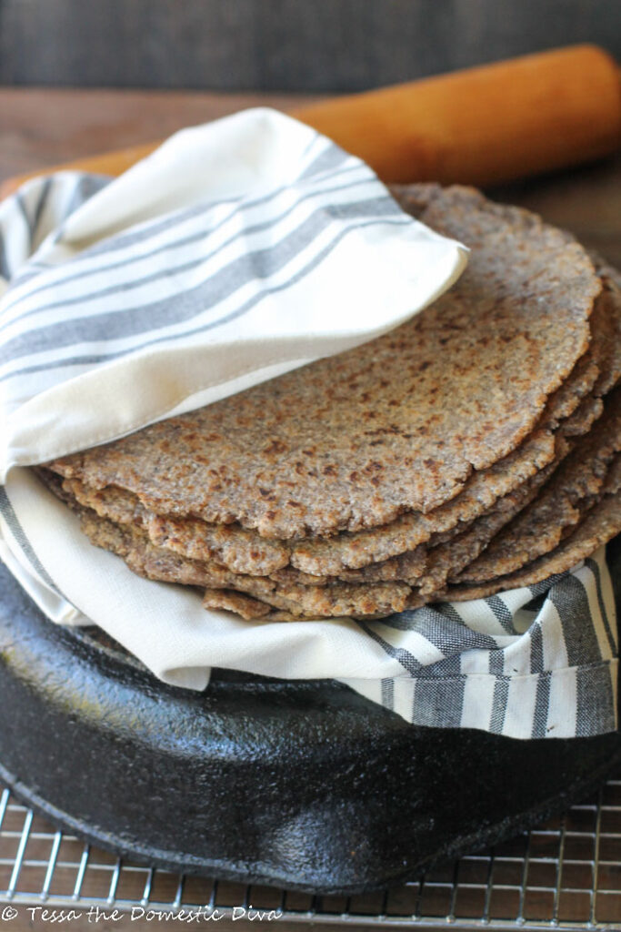 eye level stack of homemade tortillas with a rolling pin in the background