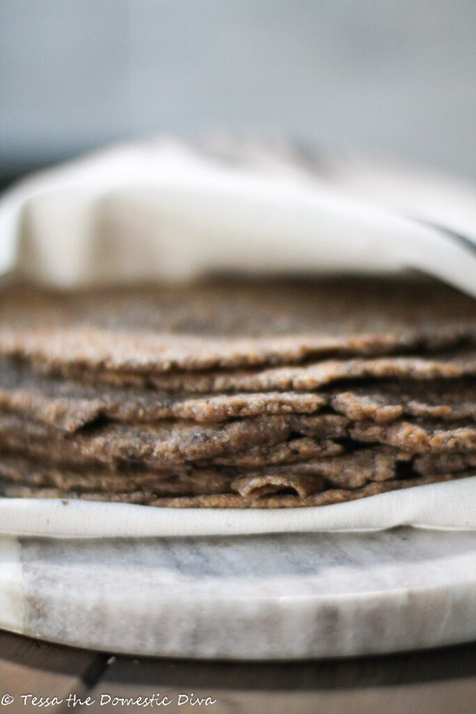 a stack of many wholegrain brown tortillas wrapped in a off white linen