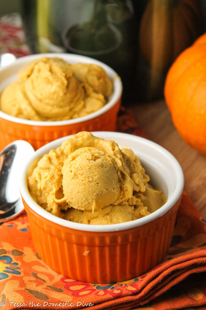 two pumpkin orange ramekins with scoops of orange hued pumpkin ice cream