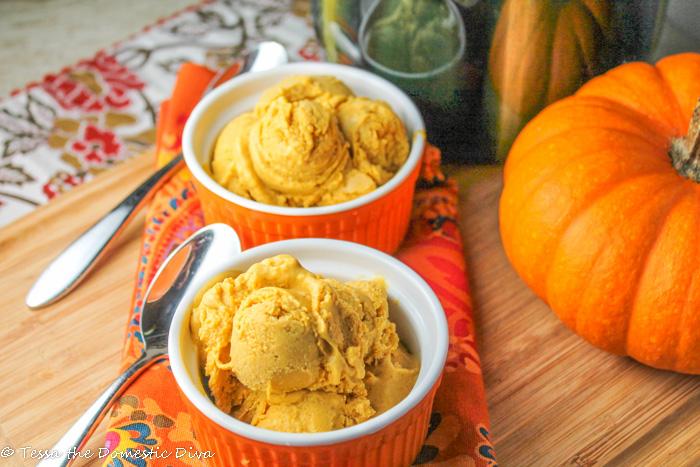 two orange ramekins filled with fresh homemade pumpkin ice cream on a wooden cutting board
