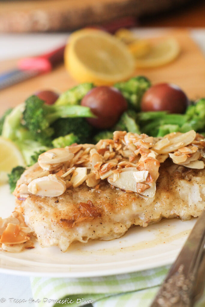 a piece of white fish crisped and topped with a butter, lemon, garlic, and almond sauce with fresh tomatoes and steamed broccoli