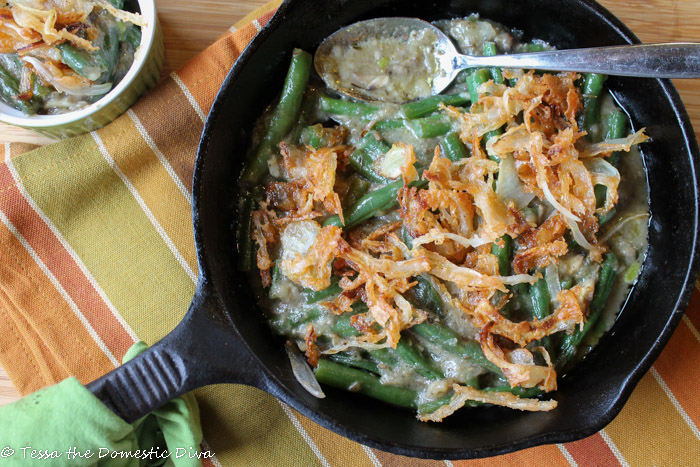 birdseye view of a black cast iron skilletfilled with bright green beans in a creamy mushroom sauce with crispy onions