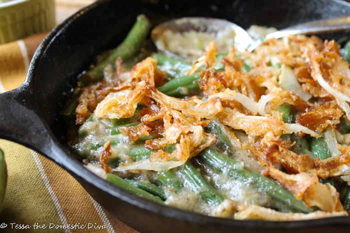 a partial close up of a black cast iron skillet filled with vibrant green beans in a mushroom sauce with crispy onions