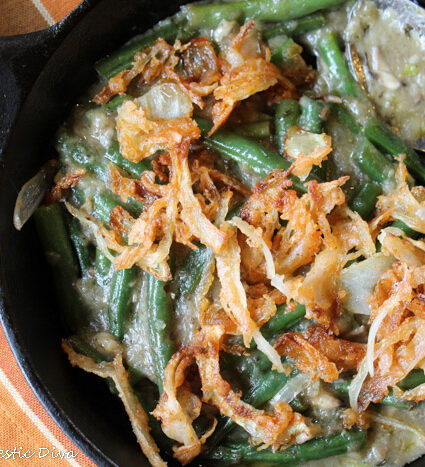 cast iron skillet filled with blancehd green beans in a creamy mushroomsauce and crispy onion topping