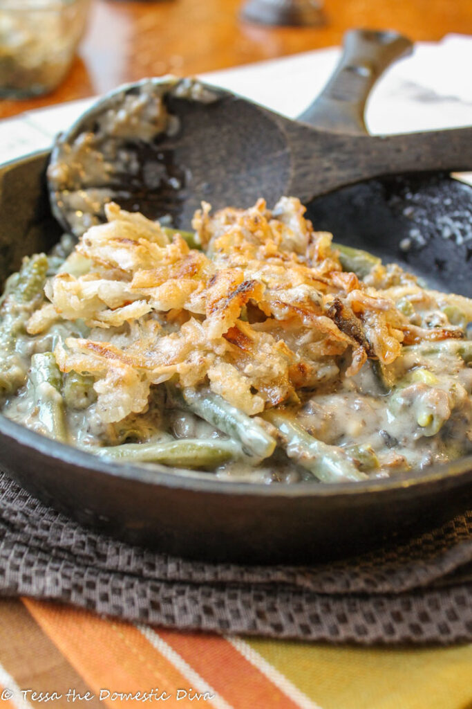 a black cast iron skillet filled with blanched green beans in a creamy mushroom sauce and topped with crispy fried onions