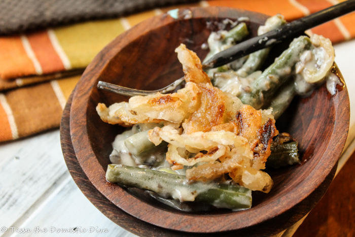 stacked dark wooden bowls filled with tender green beans in a creamy sauce with a fried onion topping