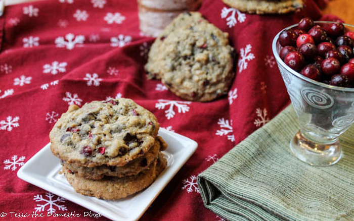 three stacked oatmeal cookies with fresh cranberries on a white plate with a red snowflake cloth