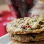 three stacked oatmeal cookies on a square white plate with a cup of fresh cranberries in background
