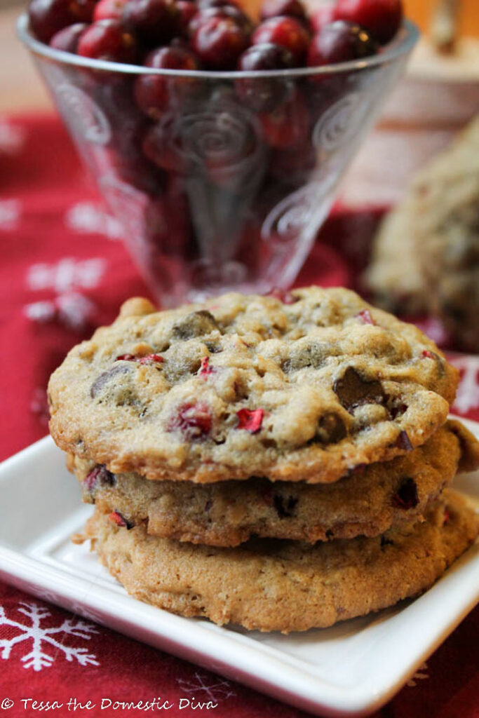 a stack of three oatmeal chocolate chip cookies with bits of chopped fresh cranberries atop a festive red snowflake cloth