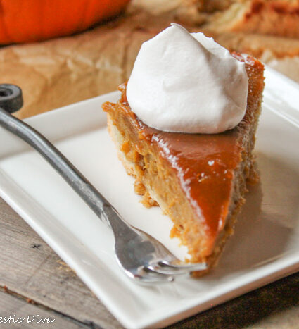 a slice of pumpkin pie on a white plate with a dollop of whipped cream