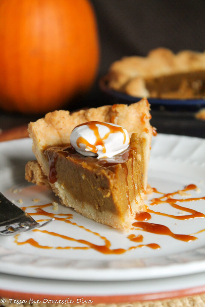 a slice of pumpkin pie of white plate with a drizzle of caramel sauce