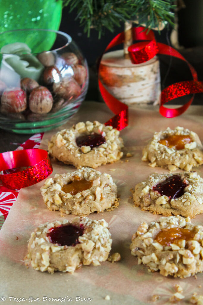 nut crusted thumbprint cookies filled with berry and apricot jam on an unbleached piece of parchment with festive Christmas ribbons and evergreen branches