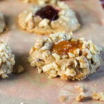 close up us a walnut coated thumbprint cookie with orange apricot jam filling on top of a holiday cloth