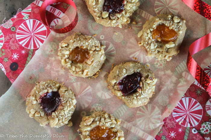 overhead view of apricot and rapsberry jam filled thumbprint coookies with a chopped walnut coating on a parchment paper and Christmas themed linen