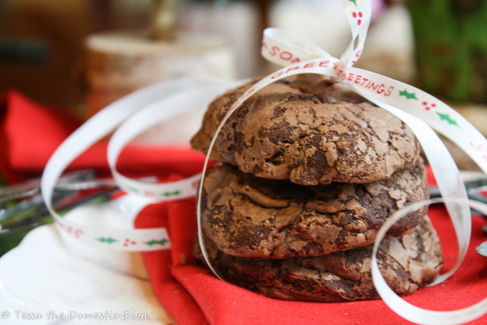 eye level of three chocolate cookies stacked on each other and wrapped with a tied seasons greetings ribbon and a silver snowflake nearby