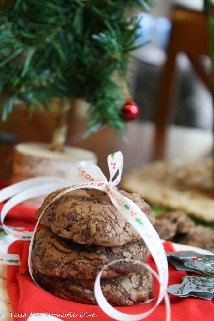 three glossy chocolate cookies stacked with a white Christmas ribbon tied around