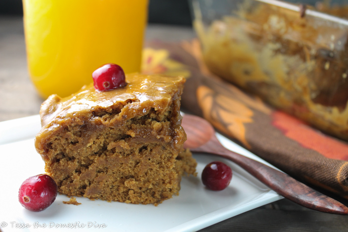a square of pumpkin cake on a white plate with fresh pumpkin puree and cranberries