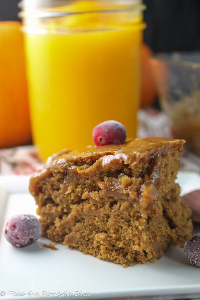 a square of moist pumpkin cake topped with a shiny caramel glaze and a fresh cranberry
