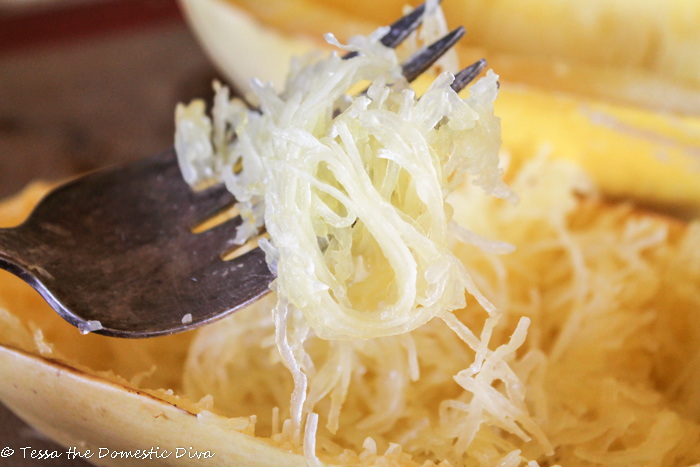 cooked threads of spaghetti squash around a fork hovering above a halved squash