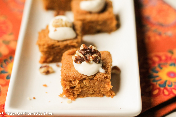 tender orange hued pumpkin cake with a dollop of brown butter cream cheese frosting and a walnut half
