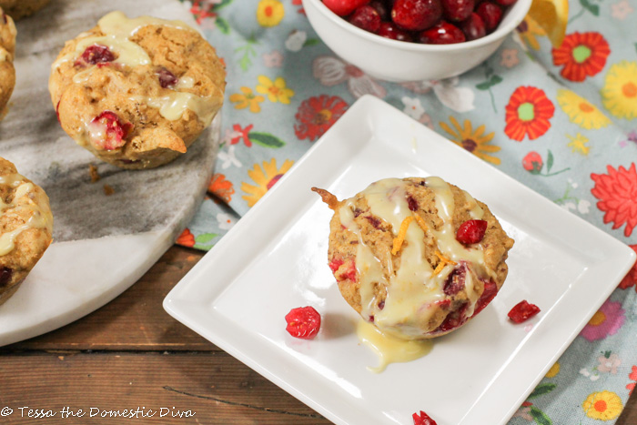 a white square plate with a cranberry studded muffin topped with a drizzle of orange glaze and zest