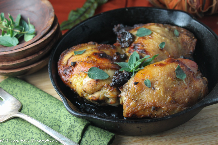 front view of three roasted chicken thighs with fresh oregani, prunes in a cast iron skillet