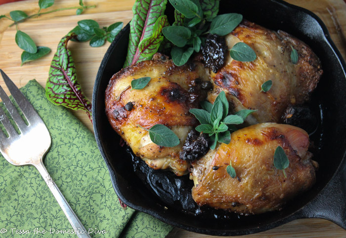 overhead view of a cast iron pan filled with three bone-in chicken thighs with crunchy skin and an oregano and prune
