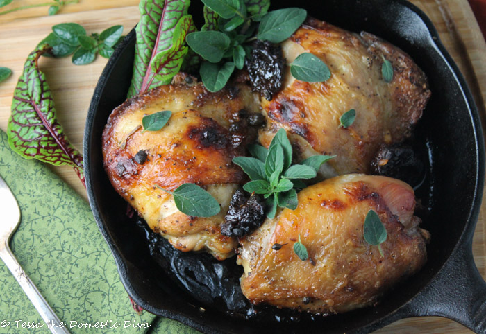 birdseye view of three roasted chicken thighs with crunchy skin in a cast iron pan with chopped prunes and fresh oregano