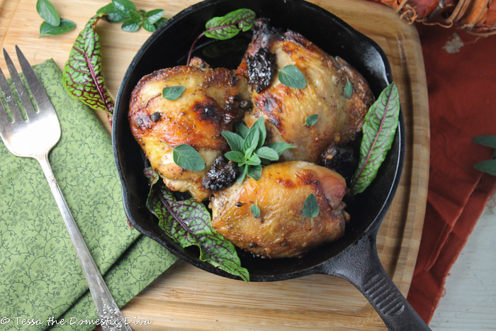 birdseye view of three crispy skinned roasted chicken thighs in a black cast iron pan with chopped prune, fresh oregano