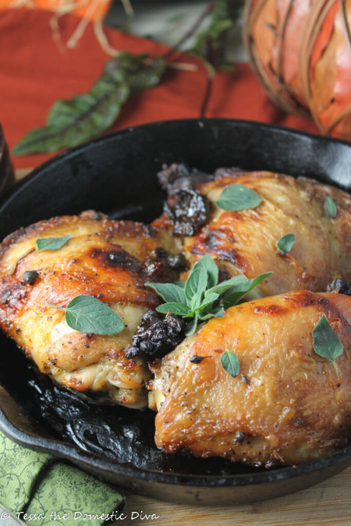 a black cast iron skillet filled with roasted chicken thighs with crispy skin and oregano, prunes. parsley
