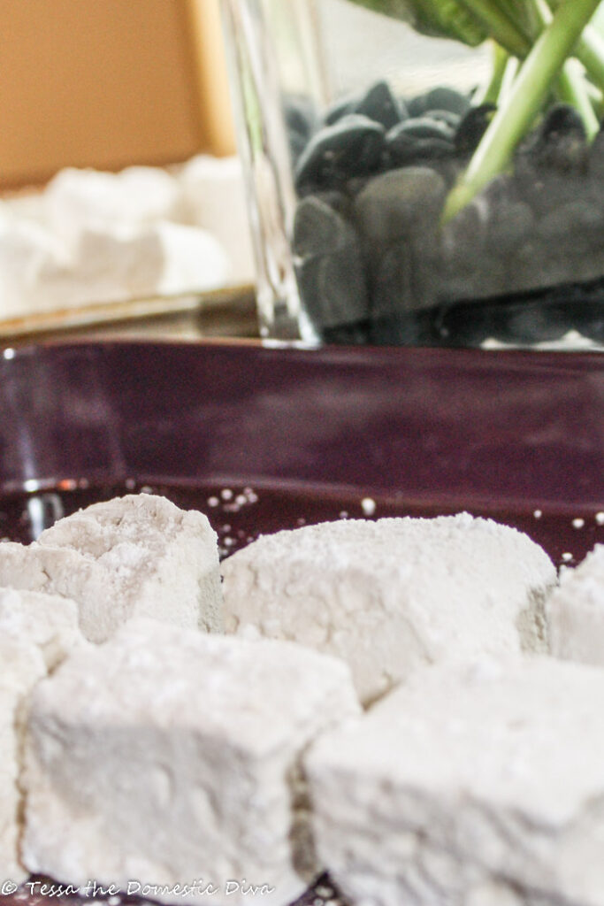 several tapioca dusted homemade marshmallows in a plum colored tray