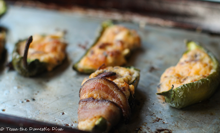 close up eye level jalapeño poppers wrapped with bacon on an distressed cookie sheet
