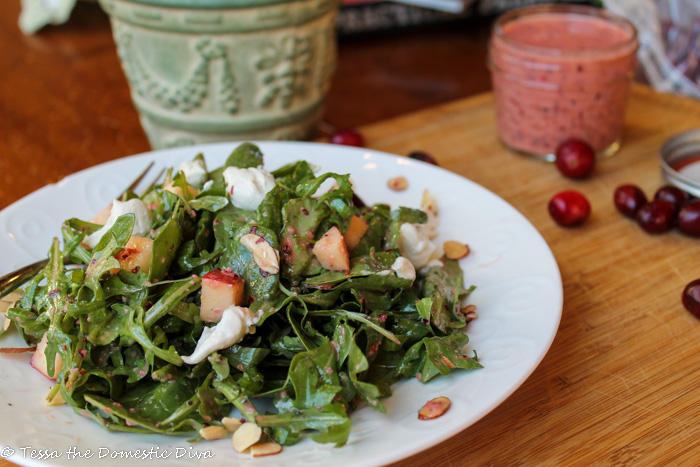 a white plate with mixed greens tossed in a bright red cranberry dressing with goat cheese and diced apples
