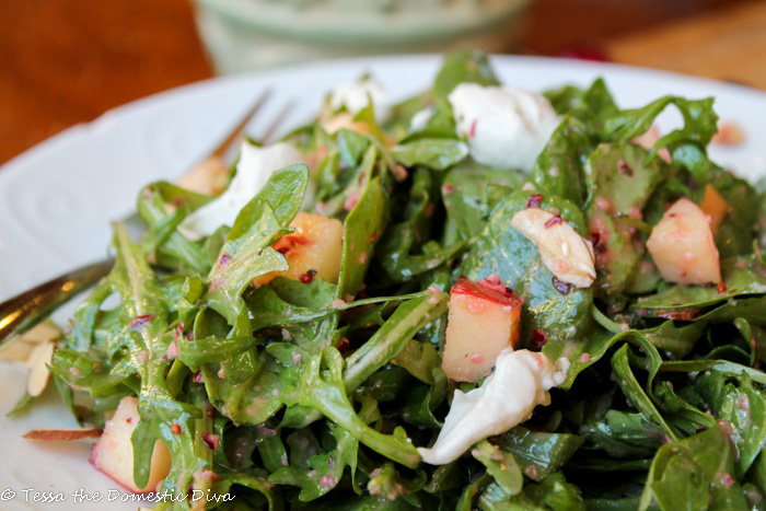 close up of mixed greens dressed in a bright red cranberry dressing with cashew cheese and diced apples