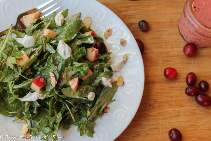 overhead view of a white salad with mixed greens topped with goat cheese, tart red apples, and a cranberry dressing