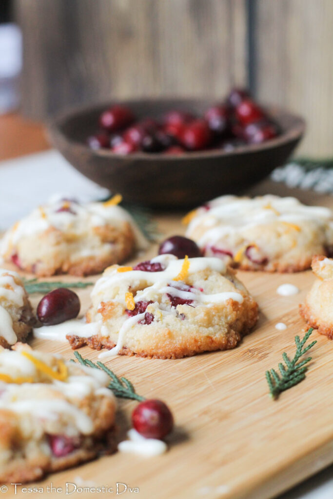 eye level view of fresh cranberry studded cookies with orange zest and cedar boughs