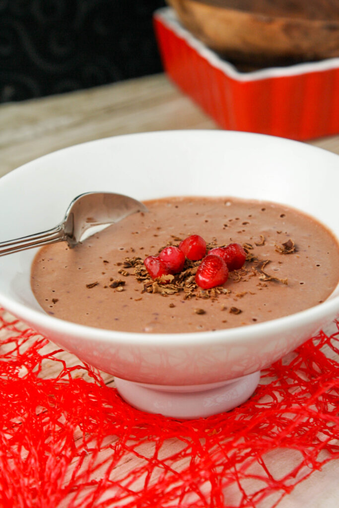 a white bowl filled with a thick chocolate mousse topped with chocolate shavings and pomegranate seeds