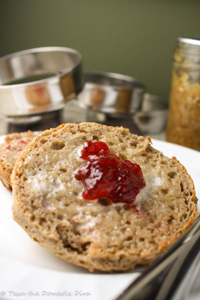 sliced wholegrain english muffin toasted with melted butter and a dollop of jam on a white plate