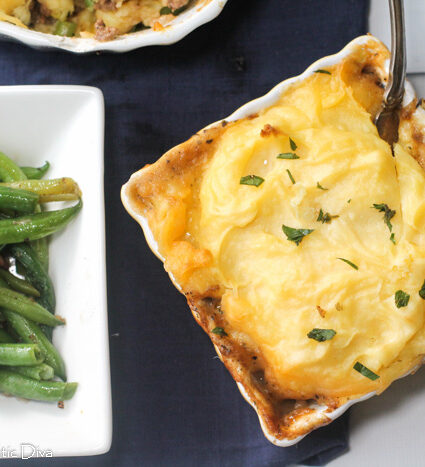 overhead view of a square ceramic baking dish with mased potato topped shepard's pie with a side of green beans