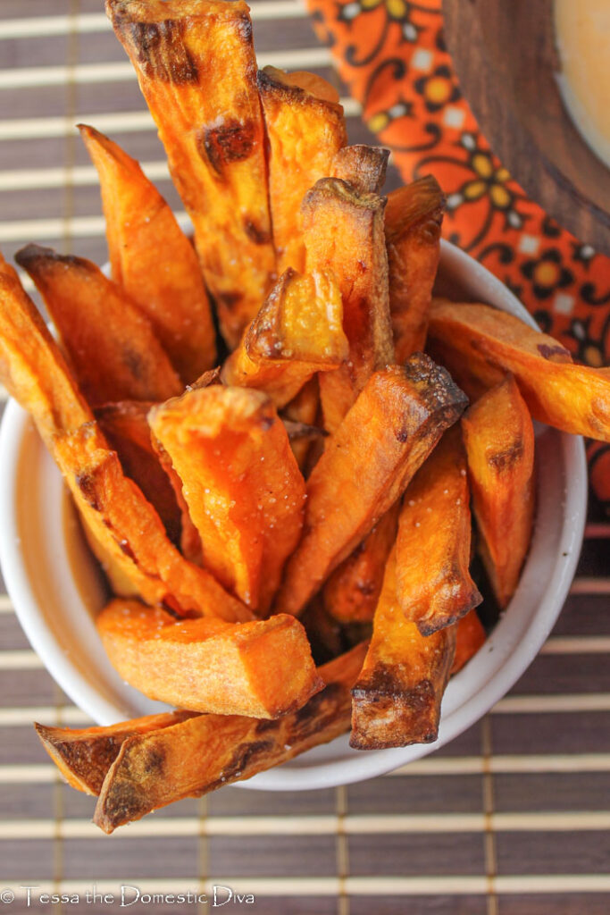 close up of crispy sweet potato fries from above on a deep orange fabric
