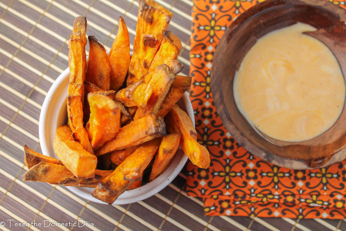 bowl of crispy sweet potato fries from above next to a sriracha mayonnaise dip