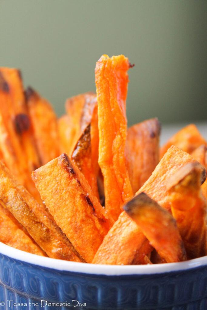 crispy sweet potato fries standing up in a dark blue ramekin