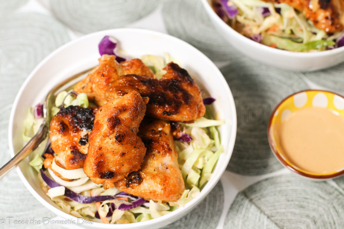 overhead shot of a white bowl filled with spicy coleslaw and breaded pan fried low carb chicken bites