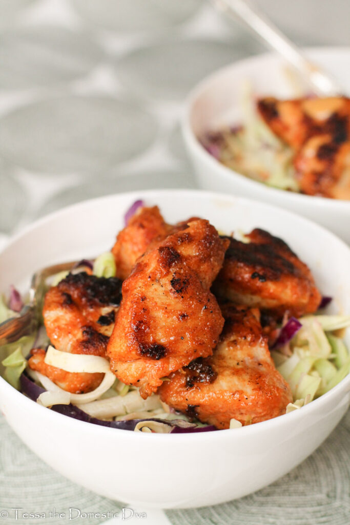 two white bowls filled with Cajun style slaw with zest pan fried chicken breast nuggets