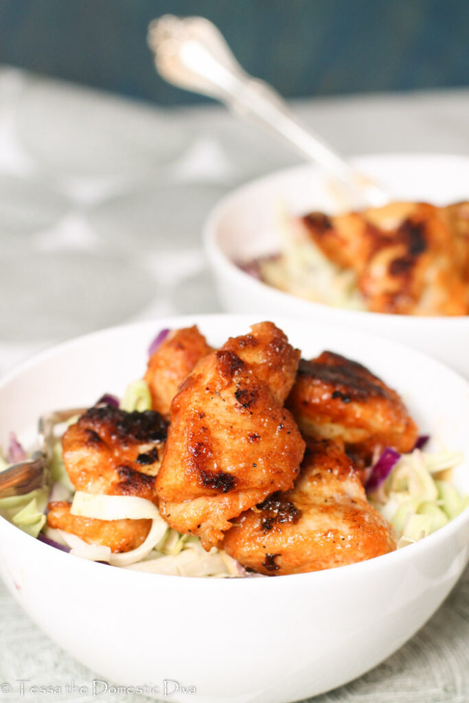 two white bowls filled with a zetsy slaw and pan fried Cajun chicken nuggets