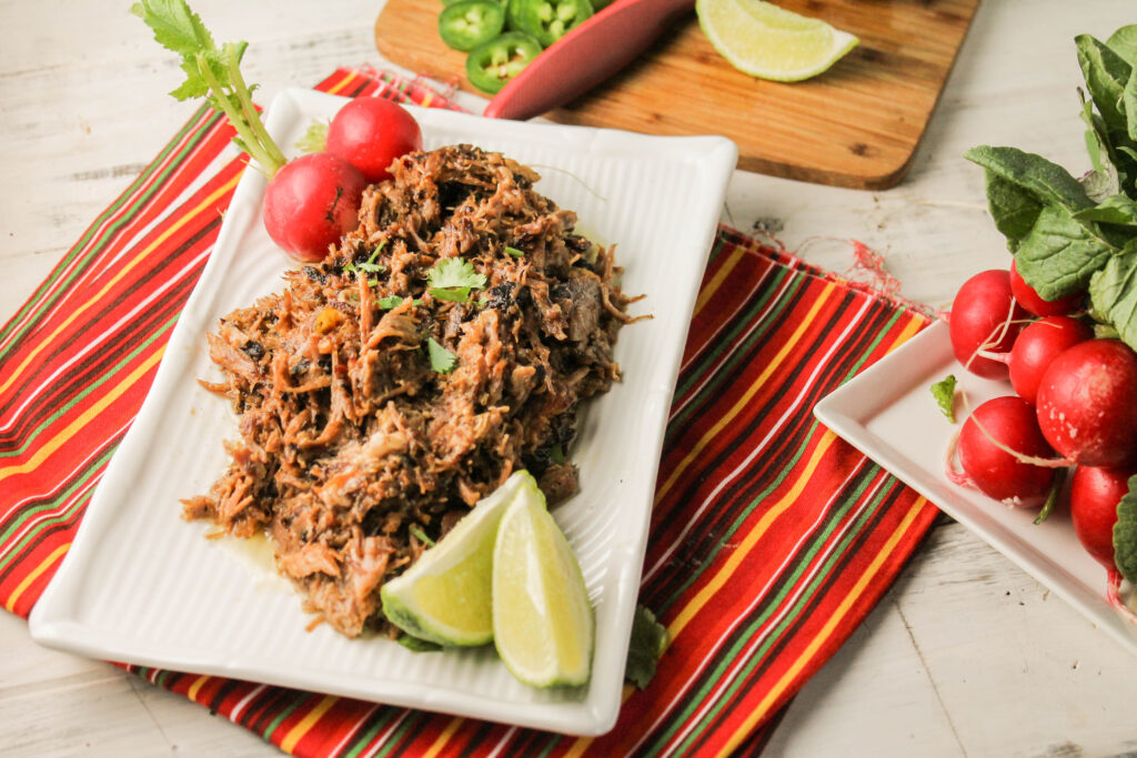 a rectangle white plate topped with crispy pulled pork with cilantro, lime, and radish garnishes