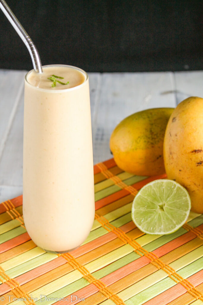 front view of a clearn tall glass with an orange smoothie topped with lime zest and fresh mango