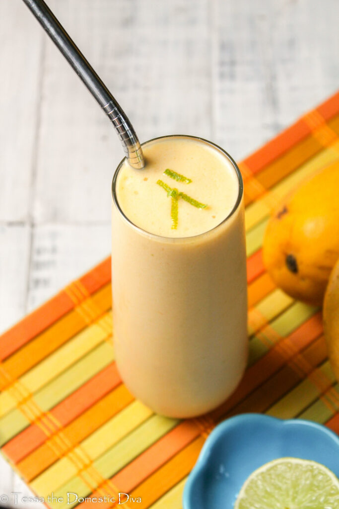 a tall clear glass filled with a creamy paleo orange smoothie with mango, lime, and kombucha