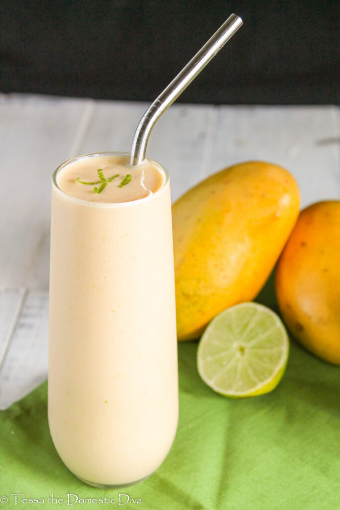 a mango, lime creamy smoothie in a tall glass with a stainless steel straw and fresh lime and Thai mangoes