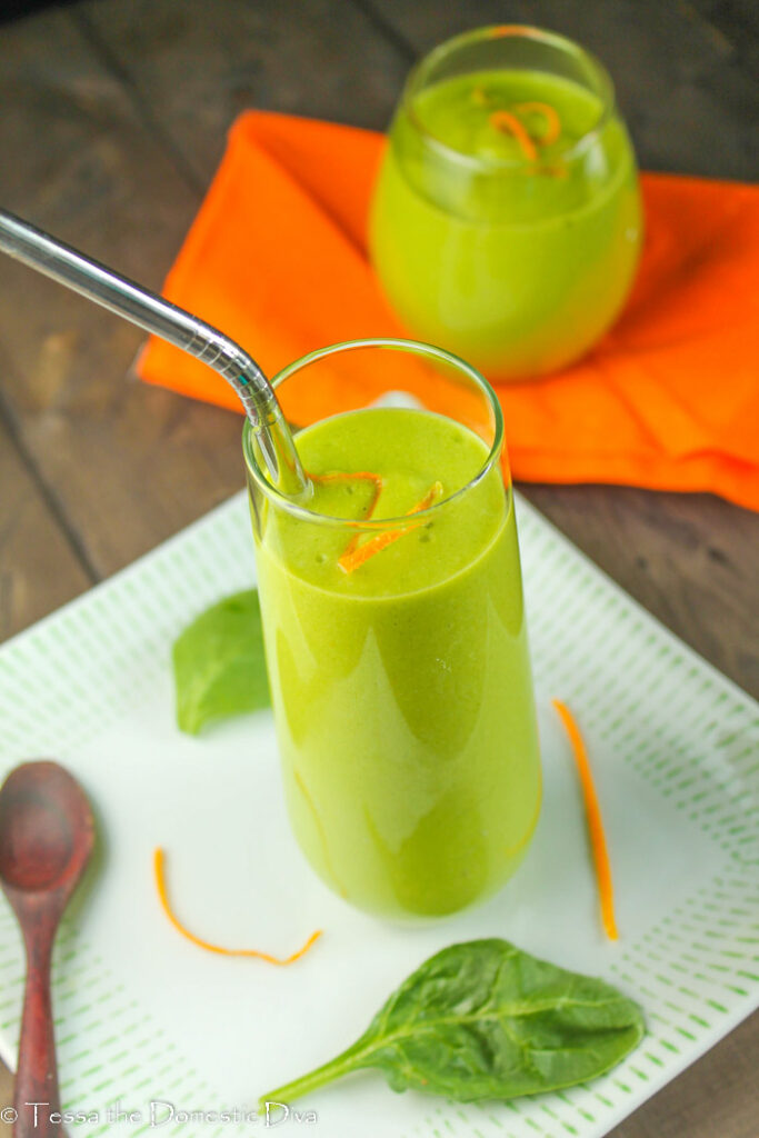 two clear glasses with a creamy green smoothie with fresh orange zest and spinach leaves